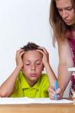 Унылая женская делая домашняя работа с ее сыном твена Стоковые Фото
