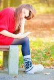 Унылая женщина в парке с телефоном Стоковые Изображения