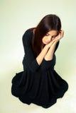 Унылая женщина в черном платье сидя на поле Стоковая Фотография RF