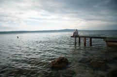 унылая женщина Депрессия маленькой девочки, стресс и проблемы, боль, отжатая женщина Молодая женщина сидя на пристани рассматрива Стоковые Фото