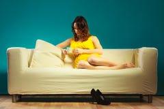 Унылая женщина сидя на кресле держит чашку Стоковое Изображение