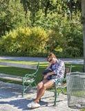 Унылая женщина сидя на скамейке в парке Стоковое Фото