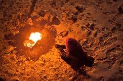 Унылая женщина сидя около костра на ноче Стоковое Изображение