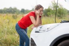 Унылая женщина смотря на сломленном автомобиле на сельской местности Стоковое Изображение