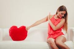 Унылая женщина с подушкой формы сердца красный цвет поднял Стоковые Фотографии RF