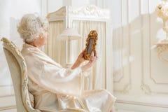 Унылая зрелая дама вспоминая в прошлом с фотоснимком стоковые изображения