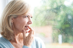 Унылая зрелая женщина страдая от агорафобии смотря из Windo стоковое изображение rf
