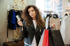 Унылая курчавая молодая дама держа кредитную карточку в сторону смотрящ Стоковые Фотографии RF