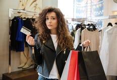 Унылая курчавая молодая дама стоя в магазине одежды ` s женщин Стоковые Фото