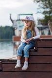 Унылая маленькая девочка сидя на пристани и взглядах на реке Стоковая Фотография
