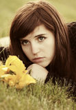 Унылая молодая женщина при цветки лежа на траве Стоковая Фотография RF