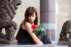 Унылая молодая женщина с красной розой Стоковые Изображения