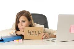 Унылая отчаянная коммерсантка в стрессе на знаке помощи удерживания стола компьютера офиса Стоковые Изображения RF