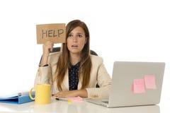 Унылая отчаянная коммерсантка в стрессе на знаке помощи удерживания стола компьютера офиса Стоковая Фотография