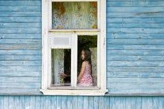 Унылая пробуренная маленькая девочка сидя на силле и смотря вне окно загородного дома Стоковое фото RF