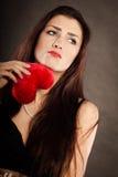 Унылая симпатичная женщина держит красное сердце на черноте Стоковая Фотография