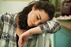 Унылая сиротливая молодая женщина сидя в кухне дома Стоковые Изображения