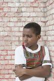 Унылая склонность против кирпичной стены, 10 лет мальчика старых Стоковая Фотография RF