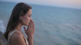 Унылая счастливая девушка молит на заходе солнца морем сток-видео