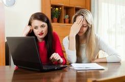 Унылые женщины с финансовыми документами и компьтер-книжкой Стоковые Фотографии RF