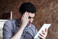 Унылый арабский бизнесмен при головная боль смотря таблетку Стоковое Фото
