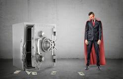 Унылый бизнесмен в красной накидке и маске стоя около сломленного strongbox при долларовые банкноты лежа вокруг стоковая фотография