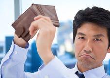 Унылый бизнесмен с его бумажником пустым перед окном офиса с пустыми карманн co Стоковая Фотография RF