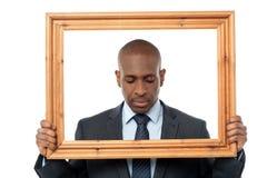 Унылый бизнесмен с деревянной рамкой стоковое изображение