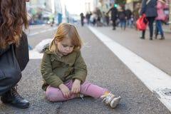 Унылый маленький ребенок сидя на улице асфальта Стоковое Фото