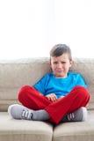 Унылый мальчик плача на софе стоковая фотография rf