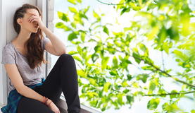 Унылый милый девочка-подросток сидя на windowsill стоковые изображения