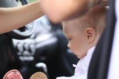 Унылый младенец в автомобиле и руках ` s женщины Стоковое Изображение RF