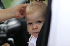 Унылый младенец в автомобиле и руках ` s женщины Стоковые Фото