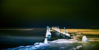 Унылый пейзаж пляжа зимы с поляками старыми волнореза Стоковые Изображения
