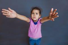 Унылый ребенок девушки смотря камеру вытягивает руки Стоковая Фотография