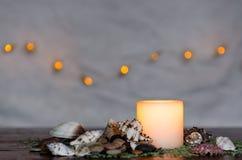 Унылый свет горящей свечи с славным пушистым светлым bokeh Улучшите для курорта Стоковое Изображение