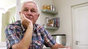 Унылый старик думая в кухне видеоматериал