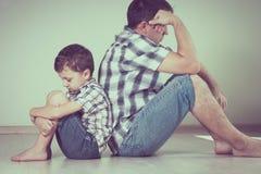 Унылый сын и его папа сидя на поле на комнате на времени дня стоковые фото