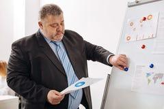 Унылый утомленный работник анализируя диаграмму Стоковые Изображения