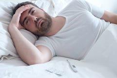 Унылый человек лежа в кровати Стоковая Фотография