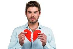 Унылый человек держа половины сердца Стоковые Фото