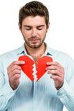Унылый человек держа половины сердца Стоковая Фотография RF