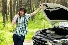 Унылый человек ждет помощь и вызывает вспомогательное обслуживание потому что его автомобиль сломал вниз стоковые фотографии rf