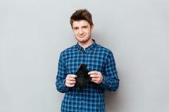 Унылый человек стоя над серой стеной держа портмоне без денег стоковое изображение rf