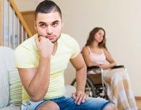 Унылый человек с подругой в инвалидном стуле Стоковые Фотографии RF