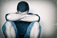 Унылый человек youg сидя на плакать пола Стоковые Изображения RF