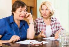 2 унылых постаретых женщины с документами Стоковые Изображения