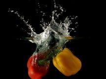 упаденные перцы под водой овощей Стоковые Фото