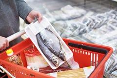 Упаковка высушенных рыб в руке на гастрономе Стоковое Изображение RF
