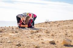 Упаковка группы Backpackers укладывает рюкзак аранжировать оборудование, каменную пустыню стоковая фотография